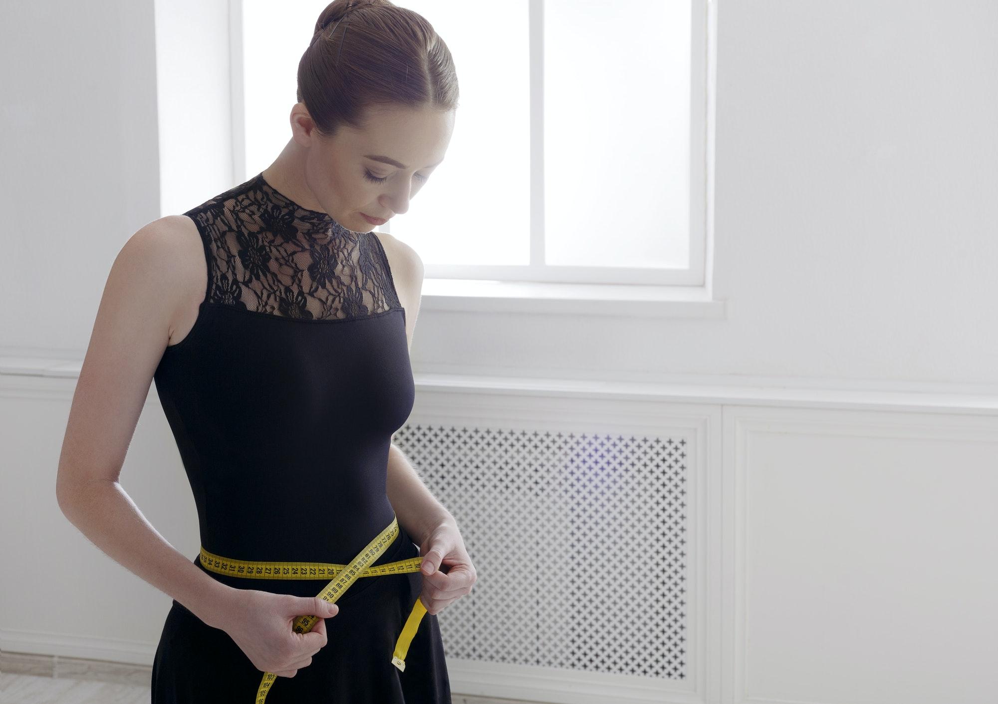 Beautiful ballerine with measuring tape, slim waist after diet